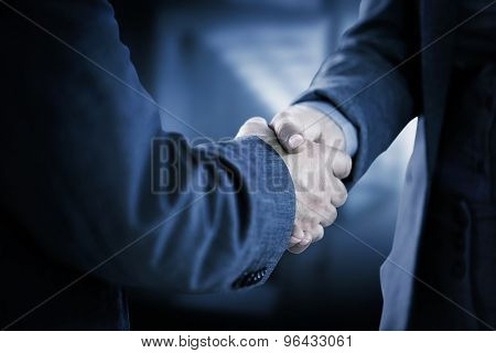 Business people shaking hands close up against stylish modern home interior with staircase