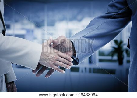 Close up of business people shaking their hands against office