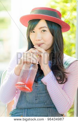 Asian Woman Drinking Strawberry Lemonade In An Cafe