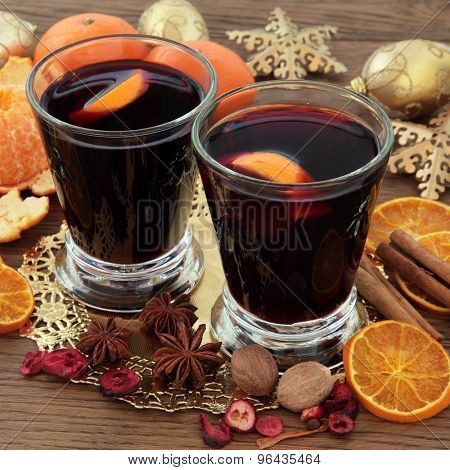 Christmas mulled wine with spices, fruit and gold baubles over oak background.