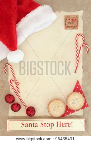 Christmas letter to santa claus with stop here sign on parchment paper with mince pies and decorations over brown paper background.