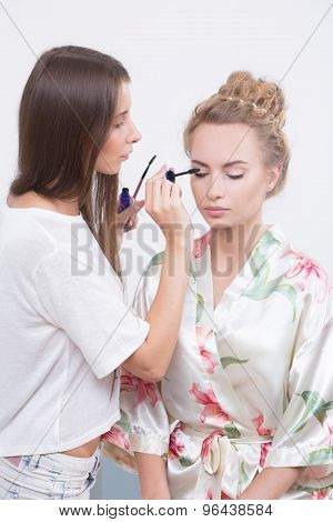 makeup artist applies mascara to the eyelashes