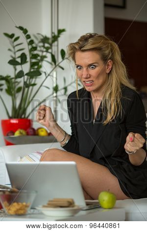 Nervous irritated young woman sitting in front of a laptop.