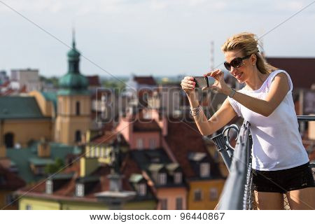 Attractive young blondie woman taking pictures on phone from lookout tower Castle Square in Warsaw, Poland.