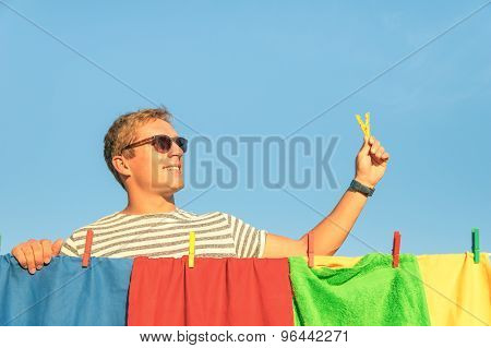 Young Handsome Hipster Man Hanging Colorful Laundry With Clothespin - Concept Of Single Lifestyle Ta