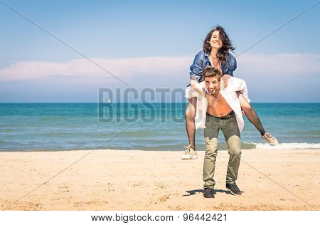 Young Couple Playing At The Beach Having Fun With A Piggyback Jump - Happy Man And Woman