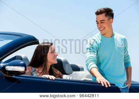 Young Man Opening Car Door To Woman.