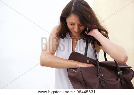 Older Woman Listening To Mobile Phone And Searching In Bag