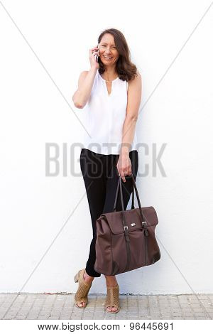 Older Woman With Bag Talking On Mobile Phone