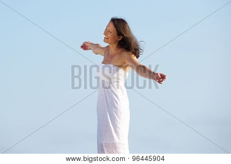 Carefree Woman Standing Outside With Arms Spread Open