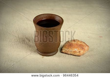 Cup of wine and bread on vintage cloth