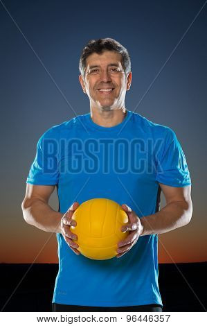 Portrait of mature hispanic man holding volleyball with sunset in background