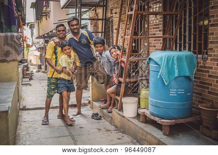 MUMBAI, INDIA - 16 JANUARY 2015: Five family members stand together in slum street. Post-processed with grain, texture and colour effect.