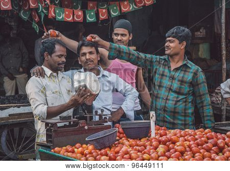 MUMBAI, INDIA - 12 JANUARY 2015: Street vendors make fun of each other. Vendor puts tomatoes into bag. Post-processed with grain, texture and colour effect.