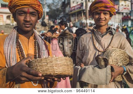 VARANASI, INDIA - 23 FEBRUARY 2015: Two Indian boys dressed up in religious clothes hold cobras in baskets. Post-processed with grain, texture and colour effect.