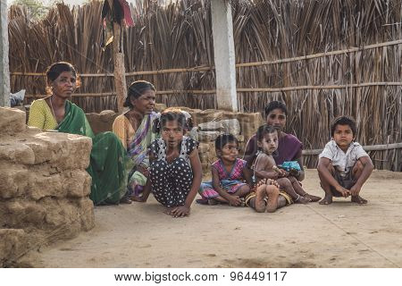 HAMPI, INDIA - 31 JANUARY 2015: indian family sitting on clean soil ground in evening shade. Post-processed with grain, texture and colour effect.