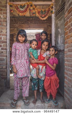 GODWAR REGION, INDIA - 15 FEBRUARY 2015: Six girls from same family stand in doorway under decorated door arch. Post-processed with grain, texture and colour effect.