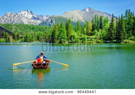 Father with child rowing in paddle boat