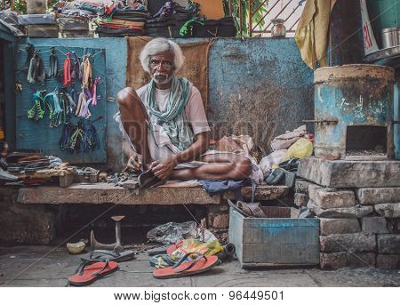 VARANASI, INDIA - 25 FEBRUARY 2015: Indian vendor sits in street shop and repairs slippers. Post-processed with grain, texture and colour effect.