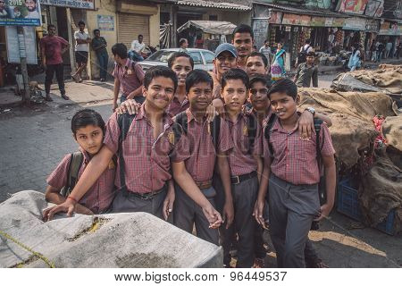 MUMBAI, INDIA - 16 JANUARY 2015: Schoolboys dressed in uniform gather around for a photograph in slum street. Post-processed with grain, texture and colour effect.