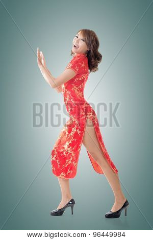 Chinese woman dress traditional cheongsam and push something at New Year, full length portrait isolated.