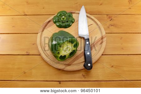 Green Pepper Sliced Open With A Knife On A Chopping Board