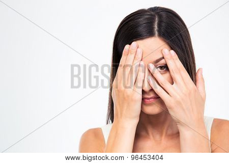 Woman looking at camera through fingers isolated on a white background