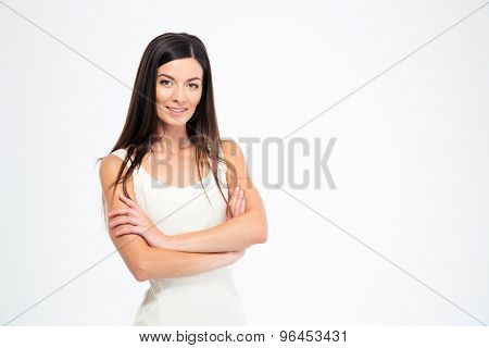 Portrait of a happy woman standing with arms folded isolated on a white background. Looking at camera