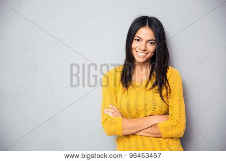 Portrait of a happy young girl standing with arms folded over gray background and looking at camera