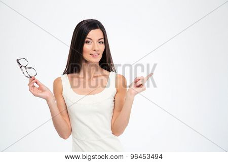 Hapyp woman holding glasses and pointing finger away isolated on a white background