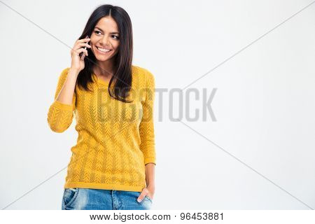 Happy beautiful woman talking on the phone isolated on a white background. Looking away