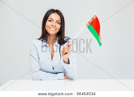 Smiling businesswoman sitting at the table with belorussian flag isolated on a white background