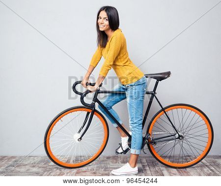 Full length portrait of a smiling woman with bicycle on gray background. Looking at camera