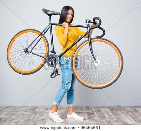 Smiling young woman holding bicycle on shoulder on gray background. Looking at camera