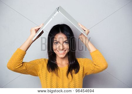 Happy woman in sweater holding laptop above her head like a roof over gray background. Looking at camera