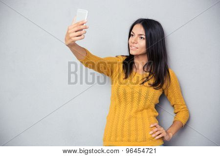 Happy woman making selfie photo on smartphone over gray background