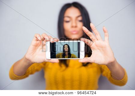 Young beautiful woman making selfie photo on smartphone. Focus on smartphone