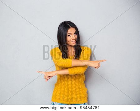 Smiling young woman showing fingers in different directions over gray background. Looking at camera