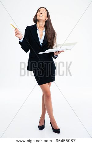 Full length portrait of a laughing woman holding paper with documents and looking up isolated on a white background