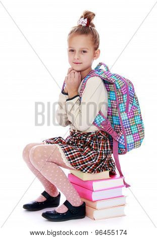 Girl sitting on rows of books