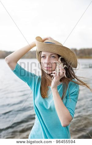 Freckled Girl In Hat Listening To Shell And Standing On Lake