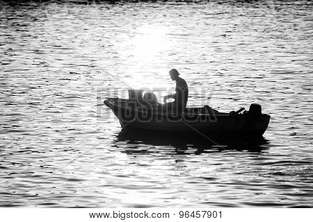 Man In Motor Boat At Sunset Bw