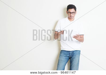 Portrait of handsome Indian guy using tablet pc, standing on plain background with shadow, copy space at side.