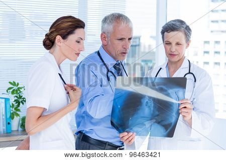 Concentrated medical colleagues examining x-ray together in the hospital