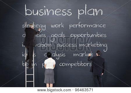 Business team writing against blackboard