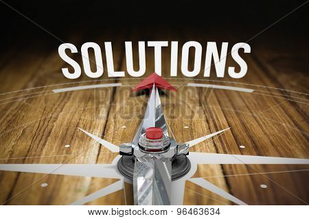 The word solutions and compass against wooden table