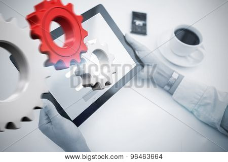 Man using tablet pc against white and red cogs and wheels