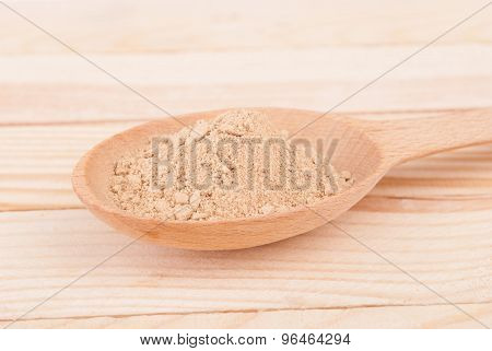 Nutmeg In A Spoon On A Wooden Table.