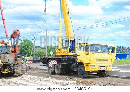 Auto crane Kamaz 55713-1. Crane driver works to set precast concrete piles for repair road