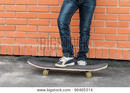 Skateboarder Standing With Skateboard Near The Wall.